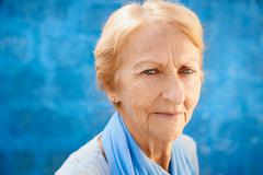happy old blond woman smiling and looking at camera - stock photo