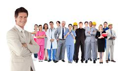 Stock Photo of Businessman standing in front of different types of workers