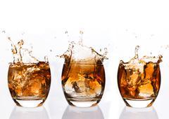 Serial arrangement of whiskey splashing in tumbler Stock Photos
