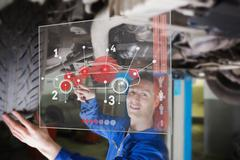 Mechanic under car consulting interface - stock photo