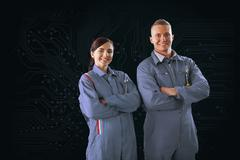 Mechanics standing in front of a circuit board background - stock photo