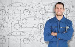 Young mechanic standing in front of cars background Stock Photos