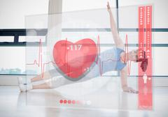 Woman doing yoga while looking at futuristic interface showing her heartbeat - stock photo