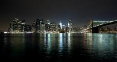 the new york city skyline w brooklyn bridge and freedom tower - stock photo