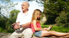 Grandfather Fishing while Granddaughter Uses Touch Screen Computer Stock Footage
