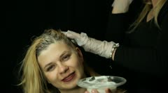 Female hairdresser bleaching hair Stock Footage