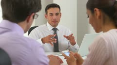 Hispanic businessman explaining the deal to couple - stock footage