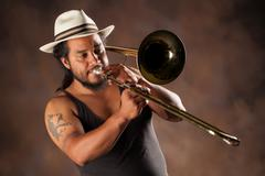 Rastafarian Man Playing Trombone Wearing A Panama Hat - stock photo