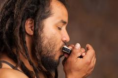 Rastafarian Man Playing Mouth Harmonica - stock photo