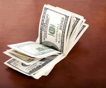 folded 100 us$  bills stack on brown background - stock illustration