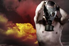 portrait of a man in a polluted ambience with gas mask - stock photo