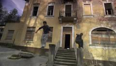 SLOW MOTION: Free runners running out of the abndoned house Stock Footage