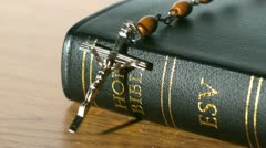 Rosary beads falling onto bible on a table Stock Footage