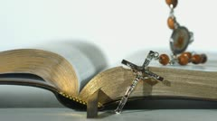 Rosary beads falling on open bible on white background close up Stock Footage