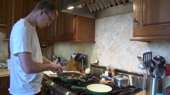 Young Man Cooks Bacon Stock Footage