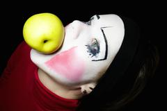 mime biting an apple on a black background - stock photo