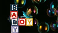 Bubbles moving over baby blocks and blue smoother on black background Stock Footage