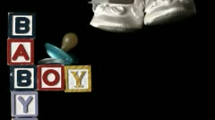 Baby shoes falling besides baby blocks and blue smoother Stock Footage
