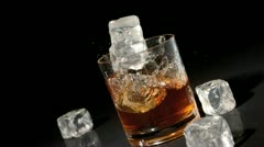 Three ice cubes falling into tumbler of whiskey and ice Stock Footage