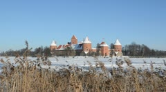 Stock Video Footage of People tourists recreate in Trakai castle snow frozen lake reeds