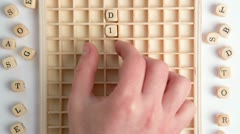 Hand spelling out diabetes message in wooden dice on grid Stock Footage