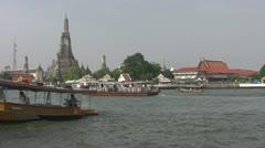 An express river taxi passes Wat Arun p57 Stock Footage