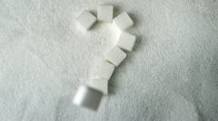 Question mark spelled out in sugar cubes forming on pile of sugar Stock Footage