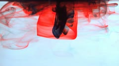Red and black ink swirling in water Stock Footage