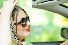 attractive woman with headscarf sitting in driver seat in the car - stock photo