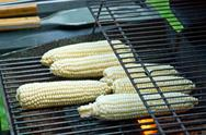 Stock Photo of Peeled raw corns on the grill