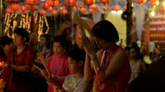 Mother and Son Praying Together at Temple on Chinese New Year - stock footage