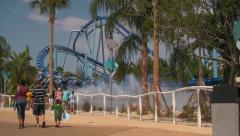 Theme Park Visitors Walking By Water Splashing Rollercoaster Stock Footage