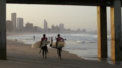 2 surfers on Durban beach at sunset Stock Footage