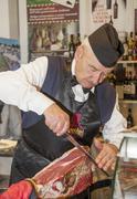 man cutting a ham - stock photo