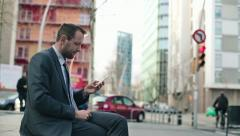 Young handsome businessman with smartphone in the city HD Stock Footage