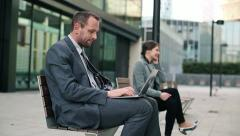 Business people with laptop and cellphone in the city HD Stock Footage