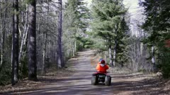 Hunting season - riding four wheeler in woods, blaze orange Stock Footage