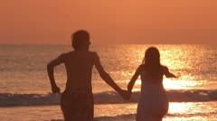 lovers run into water of the sea - stock footage