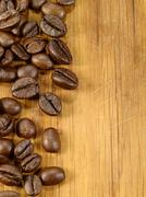 coffee beans on the wooden desk as food background - stock photo