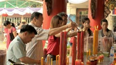 Thai People Lighting Candles at a Temple Stock Footage