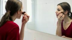 Young beautiful woman applying makeup on her face with brush HD Stock Footage