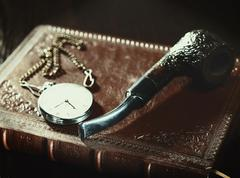 Abstract retro still life with old leather covered book and watch Stock Photos