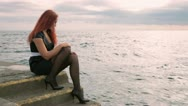 Woman sitting near the sea Stock Footage