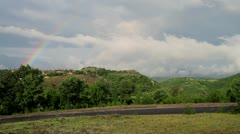 Rainbow over picturesque village Stock Footage