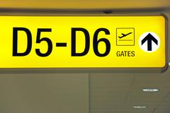 Airport departure sign showing direction to gates Stock Photos