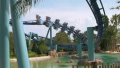 Rollercoaster Bends Close To Water with Screaming Passengers Stock Footage