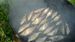 Closeup ecologic fish smoked in smokehouse and smoke rise Stock Footage