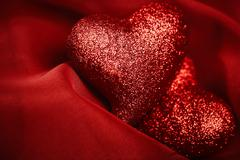 abstract valentine's backgrounds over red textile with tho hearts - stock photo