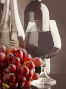 old wine. still life with wine bottles and goblet - stock photo