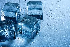Ice cube and water drops on the wet background Stock Photos